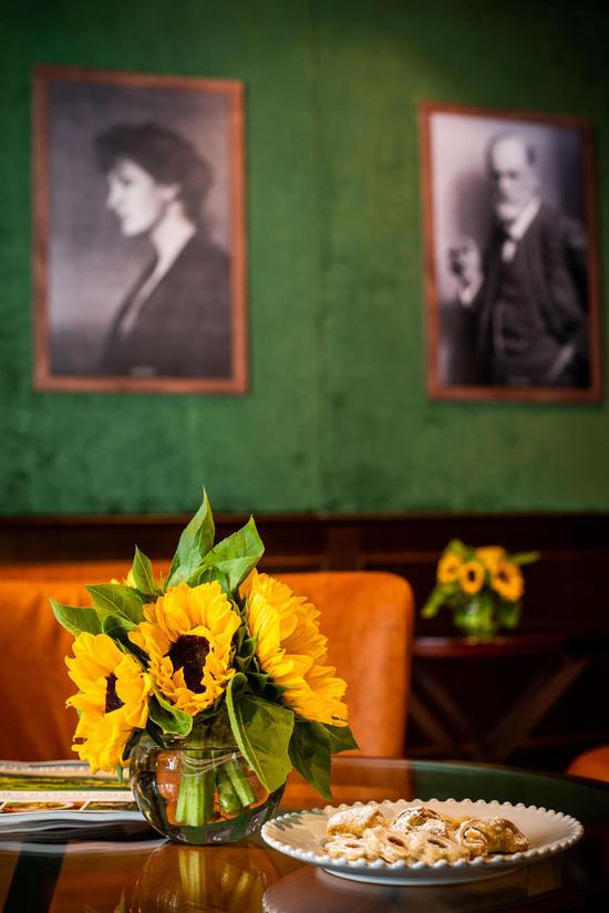 Lounge-Tisch im Jagdzimmer mit Sonnenblumen-Deko und einen Teller voll Kekse