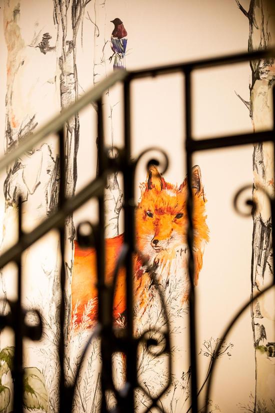 Detailaufnahme des schmiedeeisernen Geländers im Hotel Knappenhof mit Blick auf die Wandmalerei eines Fuches