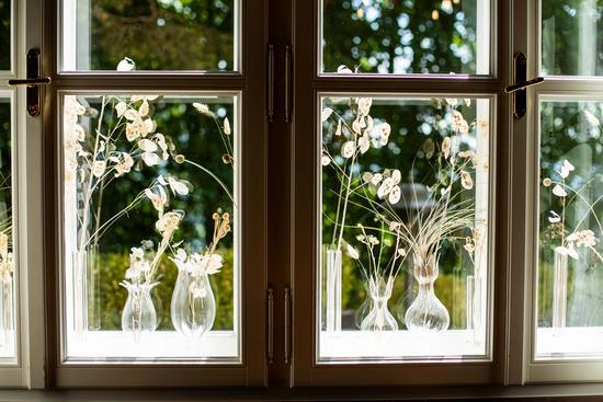 Blick durch das Fenster in den Garten mit dekorativen Elementen im Hotel Knappenhof