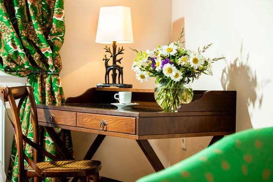 Schreibtisch mit Blumenschmuck und Tischlampe im Superior Zimmer des Hotel Knappenhof