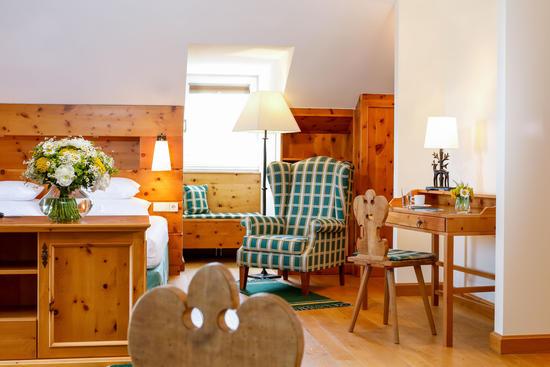 Blick auf Doppelbett, Mansardenfenster und Lesesessel in der Deluxe Suite im Hotel Knappenhof